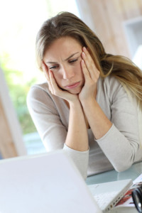 Active woman in front of laptop with upset look