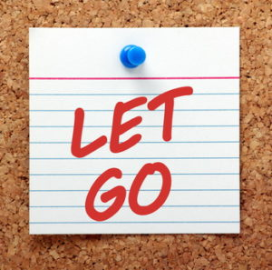 The phrase Let Go in red text on a note card pinned to a cork notice board as a reminder that sometimes we have to move on