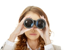 Businesswoman looking through binoculars.
