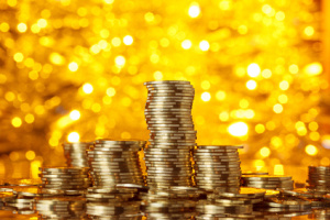 Coins stack on golden bokeh background