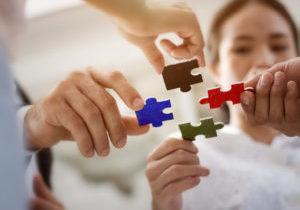 Business concept; Group of business people assembling jigsaw puzzle and represent team support and help together.
